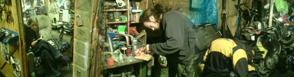 wide shot of my friend trying desperately to fix my bike in a shed-complex.