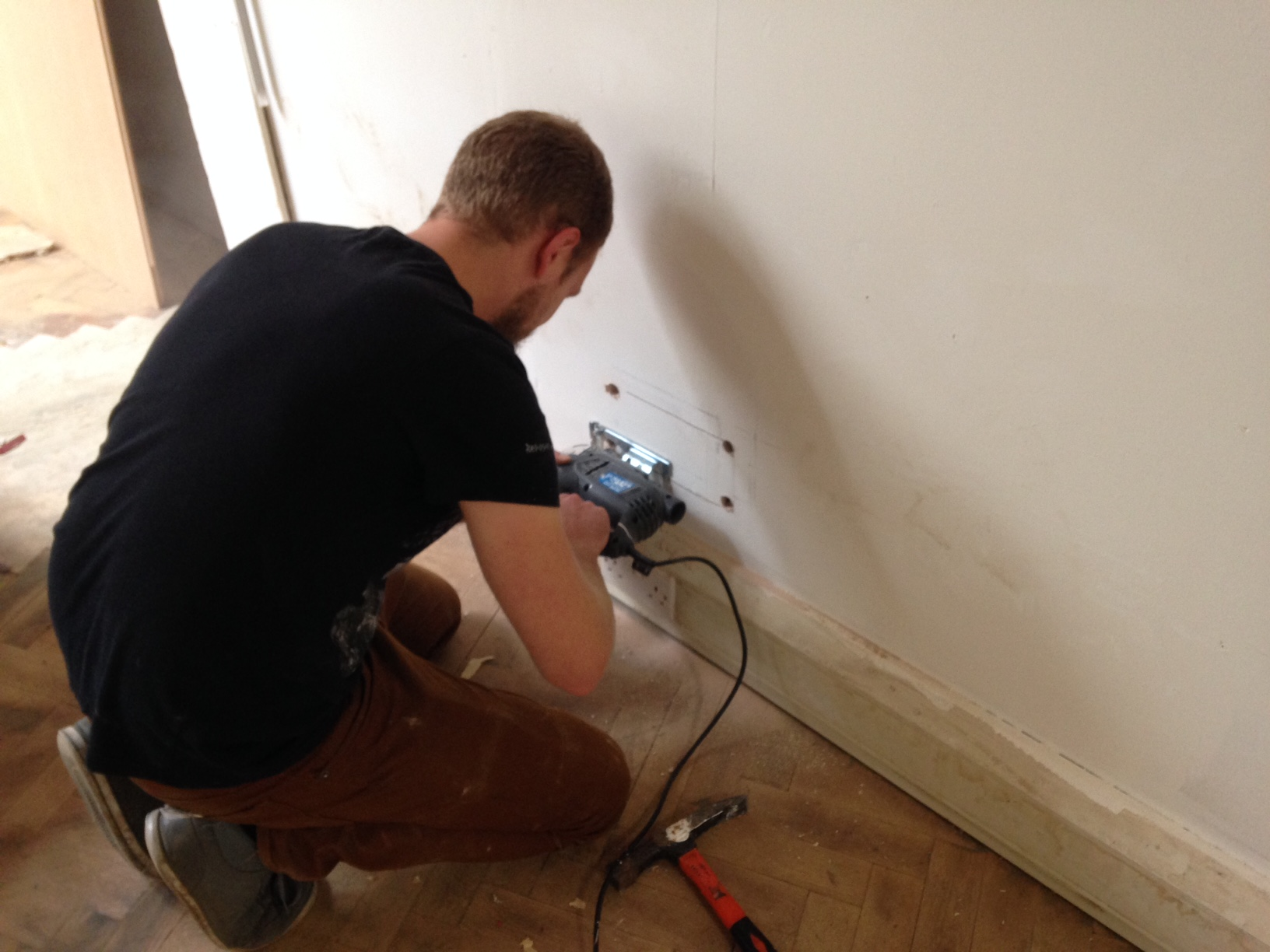 Cutting open the wall with a jigsaw to retrieve drill