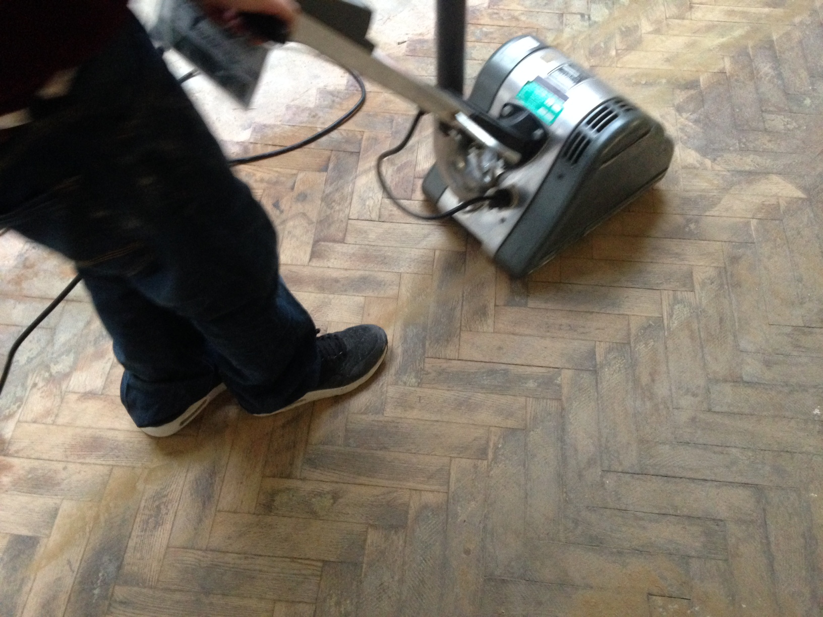 Sanding the floor with an electric floor sander